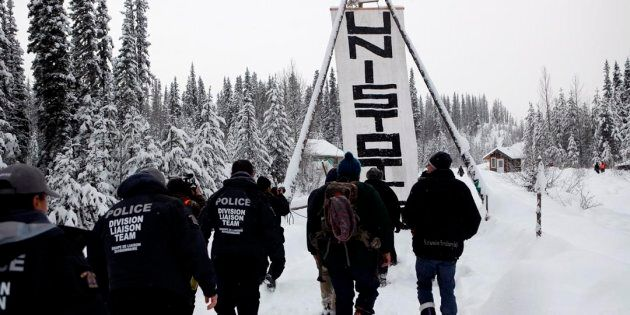 RCMP officers join hereditary chiefs and supporters as they walk towards Unist'ot'en camp near Houston,...