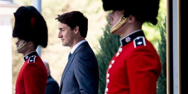 Prime Minister Justin Trudeau passes members of the Ceremonial Guard as he arrives for a press conference...