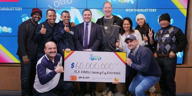 A group of coworkers poses with a giant cheque, after winning a $60-million lottery jackpot, in