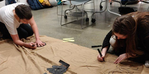 Student organizers work on a banner ahead of their event Mic Drop, a one-day activism conference held...