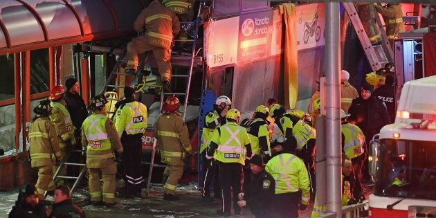 Police and first responders work at the scene where a double-decker city bus struck a transit shelter...