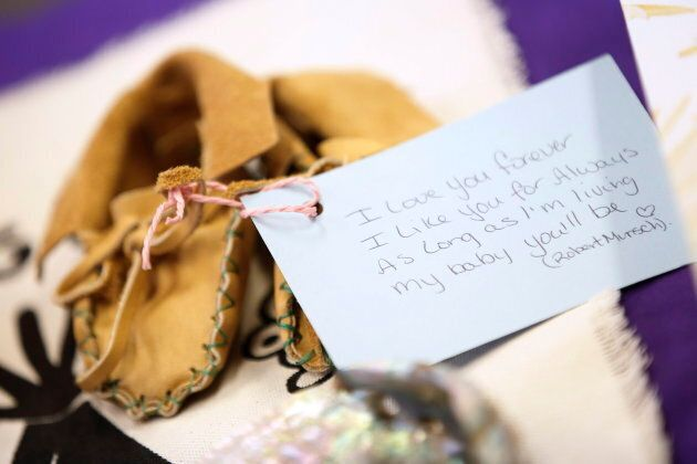 A pair of baby moccasins sit on a table during a press conference on