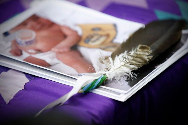 An eagle feather and a baby hospital ID bracelet sit on a photo of a newborn baby during a press