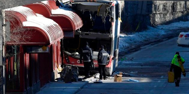 Transport Canada officials look at the scene where a double-decker city bus struck a transit shelter...