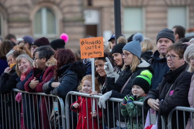 """Eliza Morris hold up her """"Gingers Unite"""" sign with a crowd of well-wishers all waiting to see Prince Harry and Meghan Markle on Monday."""