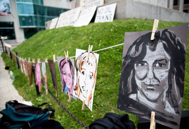 Portraits of some of the victims of the Lac-Mégantic disaster hang on a line during the a vigil held...