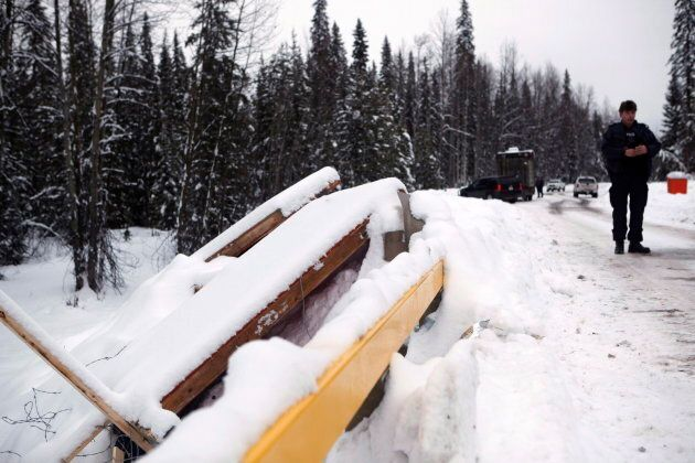 An RCMP officer looks on as remnants of the the Gidimt'en checkpoint lay by the road at the Unist'ot'en...