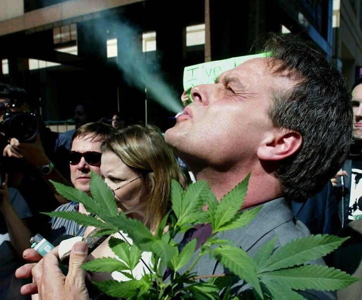 Marc Emery smokes marijuana as he holds a plant at a gathering of pro-marijuana legalization supporters outside police headquarters in Toronto on June 19, 2003.