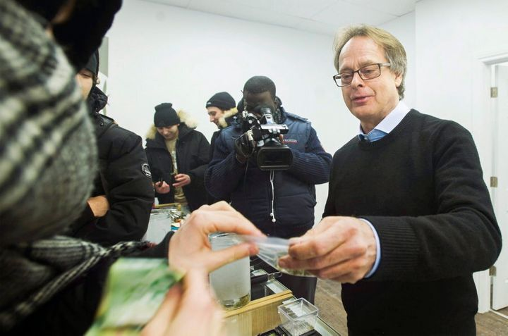 Marc Emery hands over a bag of marijuana to a customer at Cannabis Culture in Montreal on Dec. 16, 2016.