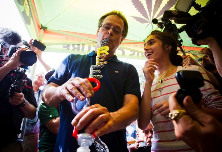 "Marijuana activist Marc Emery smokes from a bong with the words ""Freedom"" on it during a party in downtown Vancouver on Aug. 17, 2014."