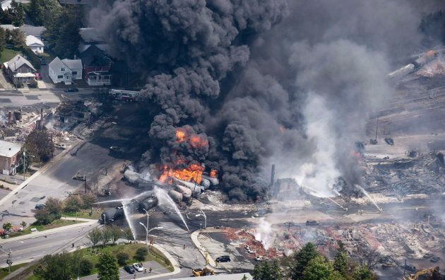 Smoke rises from railway cars that were carrying crude oil after derailing in downtown Lac-Mégantic,...
