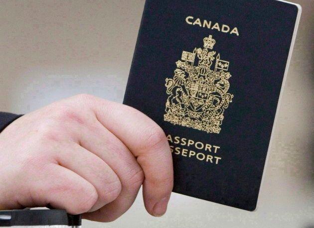 A passenger holds a Canadian passport before boarding a flight in Ottawa on Jan 23,