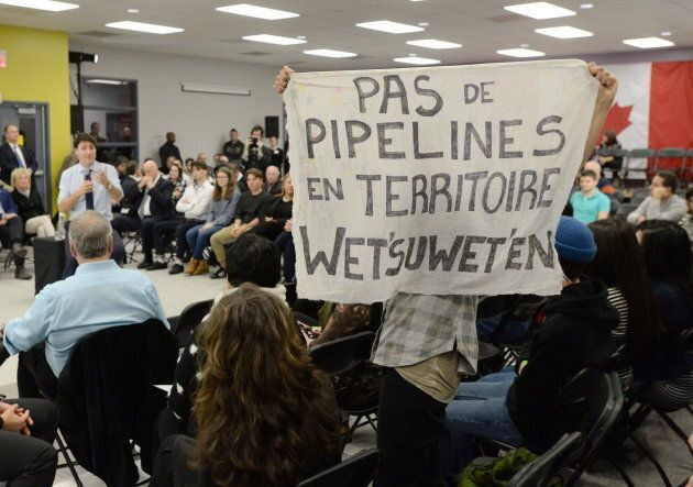 Anti-pipeline protesters ask Prime Minister Justin Trudeau a question at a a town hall meeting on