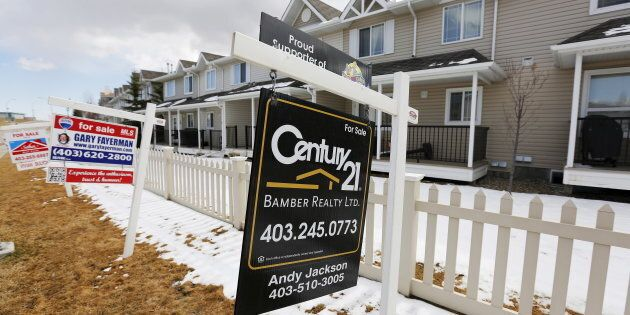 For sale signs line along a road where houses are for sale in Calgary, Alberta, April 7,