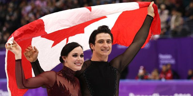 Tessa Virtue and Scott Moir of Canada celebrate during the victory ceremony for the Figure Skating Ice...