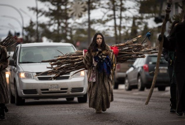 Sabina Dennis, a Dakelh woman from the Lheidli T'enneh First Nation, carries wood on her back that she...