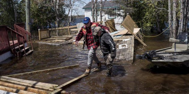 Kevin Gaddess, right, helps a friend navigate over debris from homes and cottages as floodwater continues...