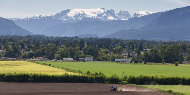 A farmer on a tractor prepares the land in Comox Valley, B.C. under the Comox
