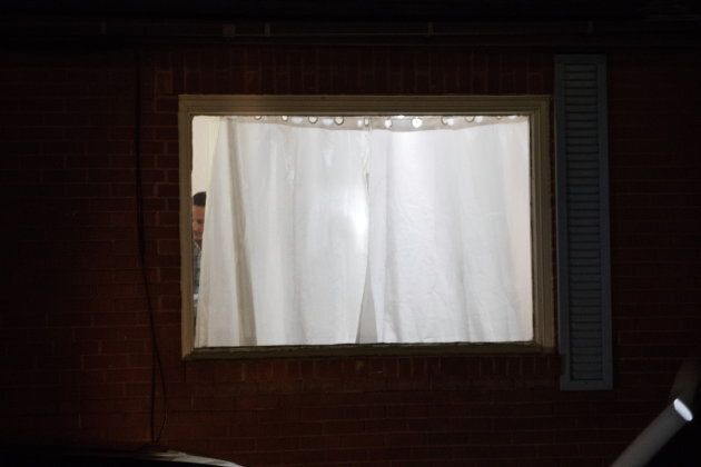 A police officer can be seen inside the house where police arrested two suspects in Kingston, Ont. on...