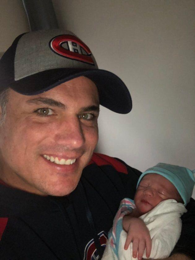 Patrick Brazeau holds his newborn son.