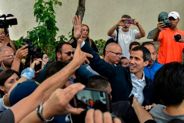 Juan Guaido waves at supporters at the San Jose church in Caracas on Jan. 27,