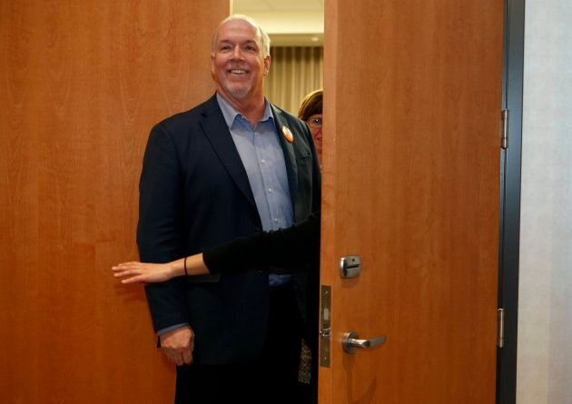 Premier John Horgan waits to walk out with NDP candidate Shiela Malcolmson after she won the byelection...