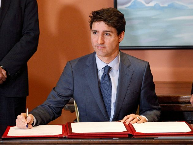 Canadian Prime Minister Justin Trudeau signs a book as he shuffles his cabinet on Jan. 14,