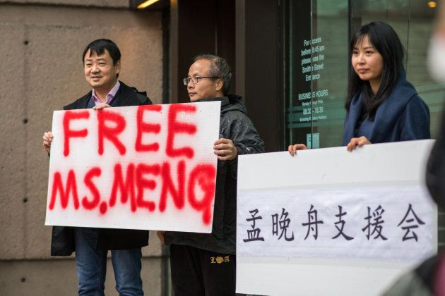 People hold signs in support of Meng Wanzhou outside of a bail hearing at the Supreme Court in Vancouver on Dec. 11, 2018.