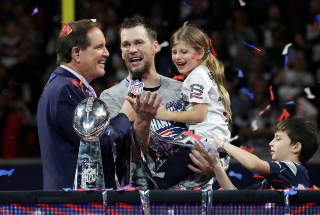New England Patriots' Tom Brady gives an interview as he celebrates alongside the Vince Lombardi Trophy...