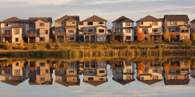 A row of houses reflected in a pond in Calgary,