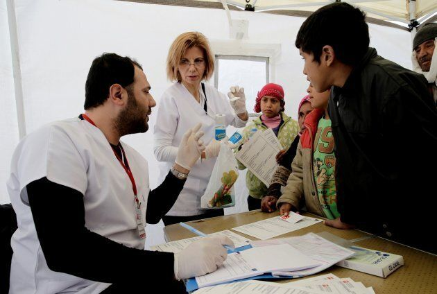 Syrian refugees wait to be examined by Doctors WorldWide Turkey at a refugee camp in the Torbali district...