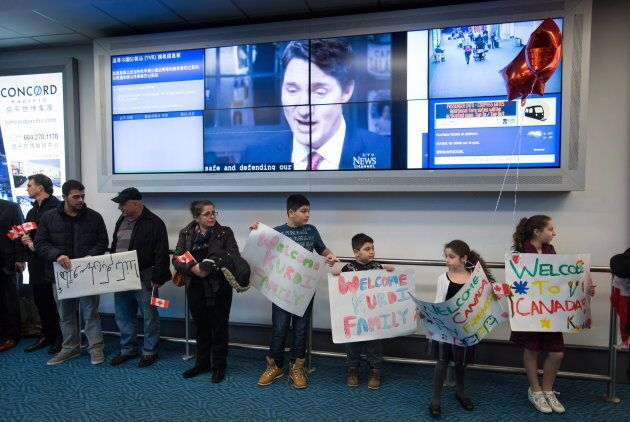 A television interview with Prime Minister Justin Trudeau plays on a screen as family and friends wait...