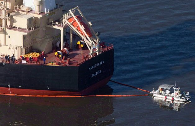 A spill response boat secures a boom around the bulk carrier cargo ship MV Marathassa after a bunker...