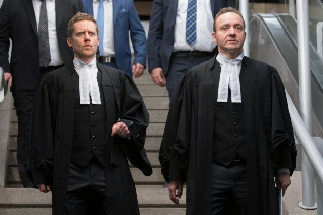 Crown prosecutors Thomas Jacques (L) and Francois Godin (R) walk before talking to the press in the Quebec...