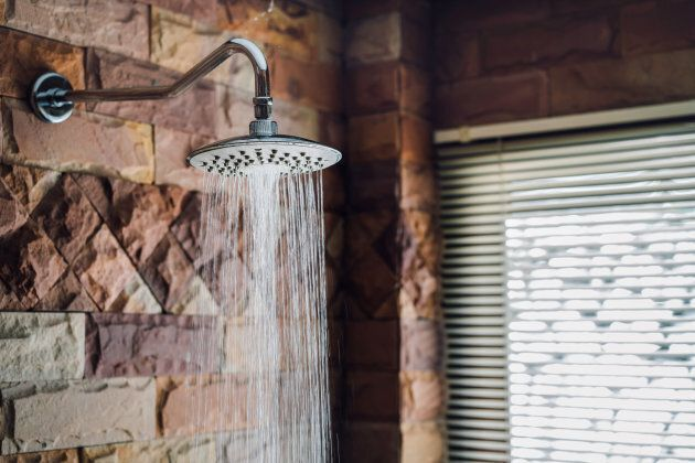 Shower in bathroom flowing water drop to the floor at modern home of brick style near window