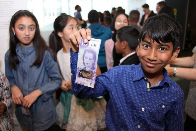 A student shows the new vertical $10 note featuring Viola Desmond, who helped start the modern civil...