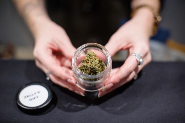 A salesperson displays a jar of cannabis at the Potorium dispensary in Nelson, B.C. on Nov. 7, 2018.