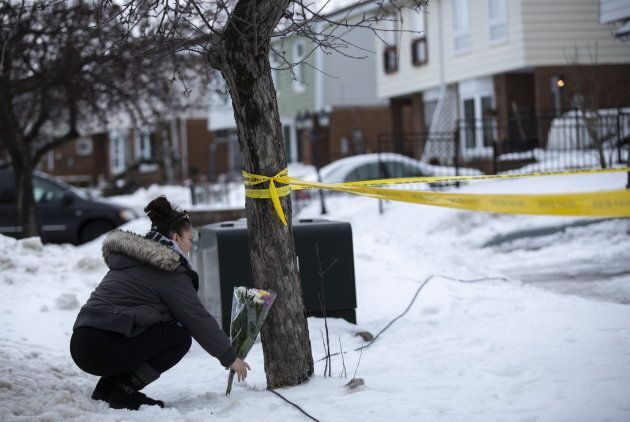 Local resident Jennifer Fuller places flowers at the scene outside of a house where a young girl was...