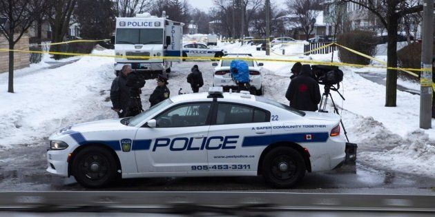 Police and media are seen near a house where a young girl was found dead in Brampton, Ont. on Feb. 15,