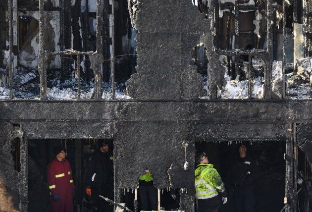 Firefighters investigate the aftermath of the fire in Halifax on Feb. 19,