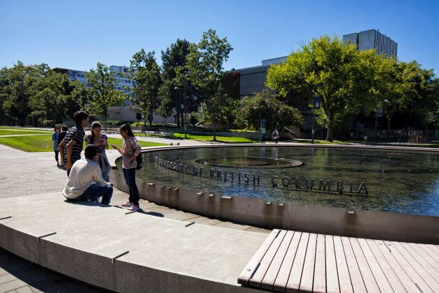 A few students seen in front of a fountain at the University of British Columbia in