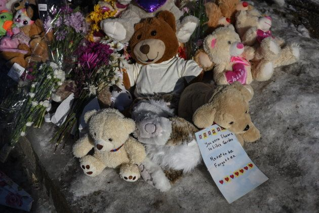 A memorial of flowers and stuffed animal toys is seen outside the scene of a fatal house fire in the...