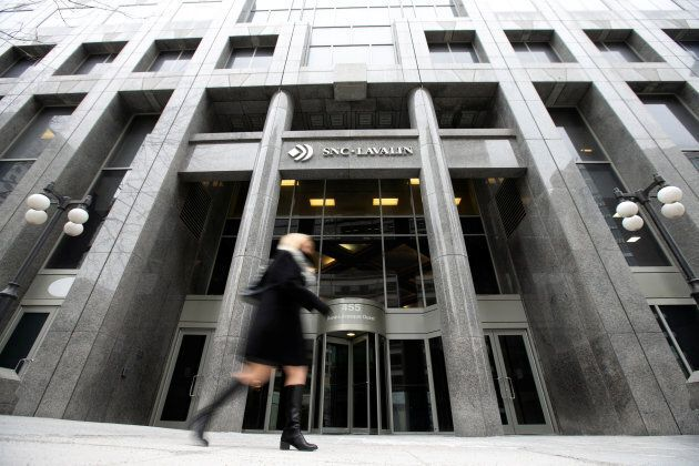 A pedestrian walks past the SNC-Lavalin Group Inc., headquarters in Montreal, Feb.12,