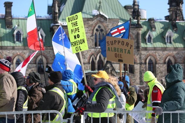 Supporters hold signs during a United We Roll Convoy pro-pipeline rally in Ottawa on Feb. 19,