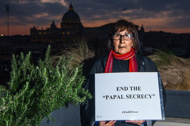 Evelyn Korkmaz, a victim from Canada, holds a sign with her message to Pope Francis on Feb. 18, 2019,...