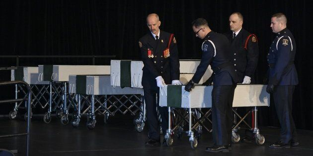 Members of the Halifax fire and police honour guard prepare to remove the caskets of the seven Barho...
