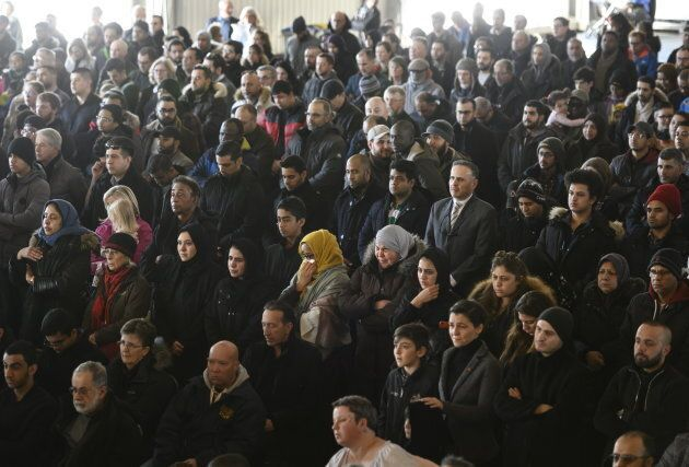 More than a thousand family, friends, and members of the community attend the funeral for the seven Syrian...