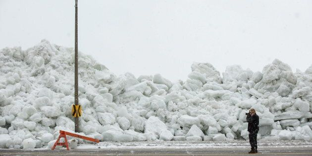 A man photographs a massive build-up of ice that was pushed onto the shore in Fort Erie, Ont., February 25, 2019.