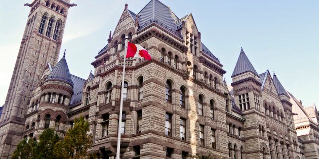 Old city hall of Toronto, Ontario, Canada with a Canadian flag and pole on the