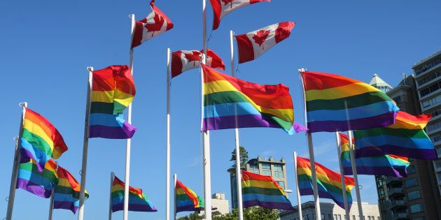 Rainbow colored gay pride flags and Canadian flags flutter in the wind beside English Bay in Vancouver's West End Neighbourhood.
